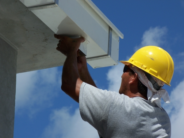 Professional roofer repairing gutters